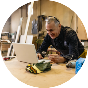 man using his laptop in his woodshop